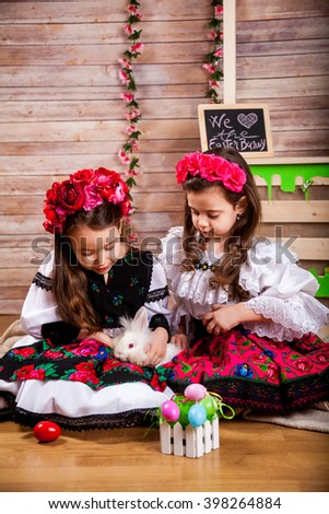 Two little girl in popular Romanian costume enjoying the Easter holidays and play with buny - stock photo