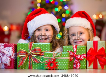 Two little girl in Santa hat hiding behind presents under the Christmas tree - stock photo
