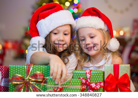 Two little girl in Santa hat playing with a gift under the Christmas tree