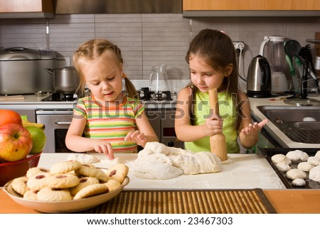 Two little girl learning how to cook - stock photo