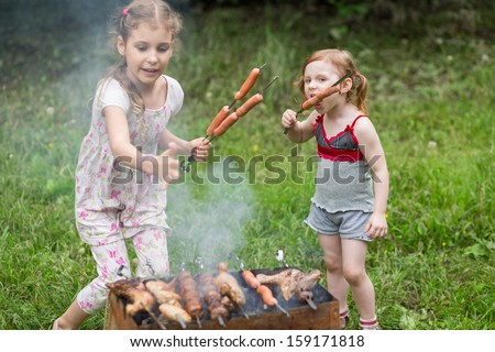 Two little girl making barbecue on the grill on nature, one girl eating a sausage on a skewer. - stock photo