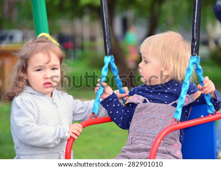 Two little girl on a swing ride - stock photo