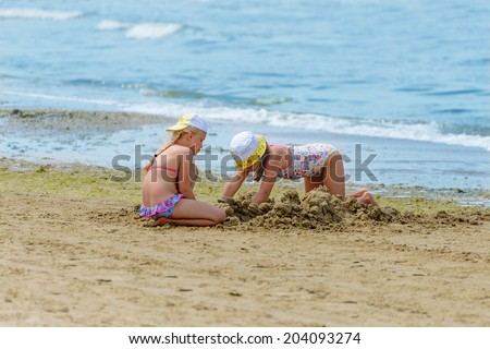 Two little girl on the beach - stock photo