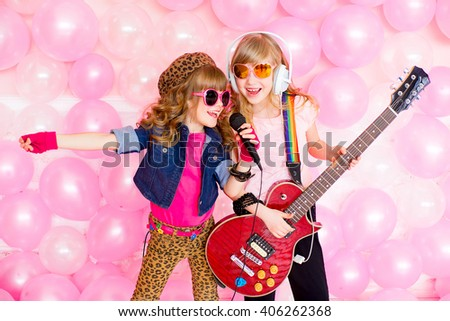 two little girl singing a song with a microphone and a guitar on a background of pink balloons - stock photo