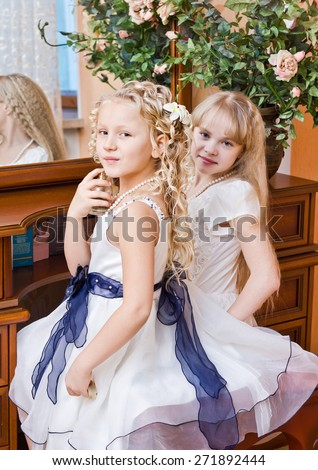 Two little girl sitting at mirror and preparing for party - stock photo