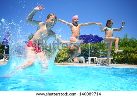 Two little girls and boy fun jumping into the swimming pool, shot through the underwater package. - stock photo