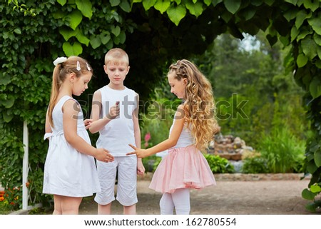 Two little girls and boy play in rock-paper-scissors standing on walkway in summer park - stock photo