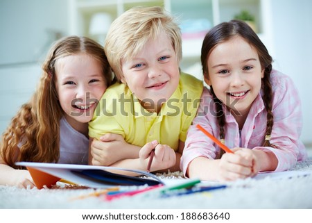 Two little girls and cute boy looking at camera while lying on the floor and drawing - stock photo