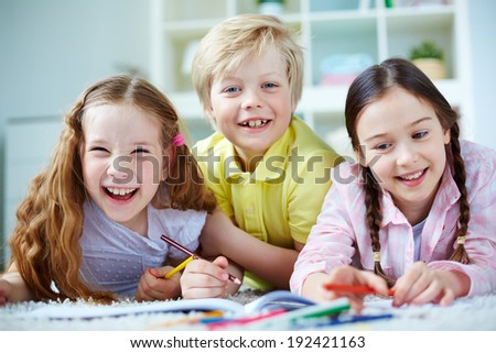 Two little girls and cute boy looking at camera while lying on the floor and drawing