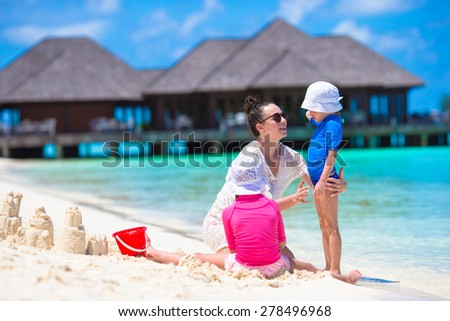 Two little girls and happy mother playing with beach toys on summer vacation - stock photo