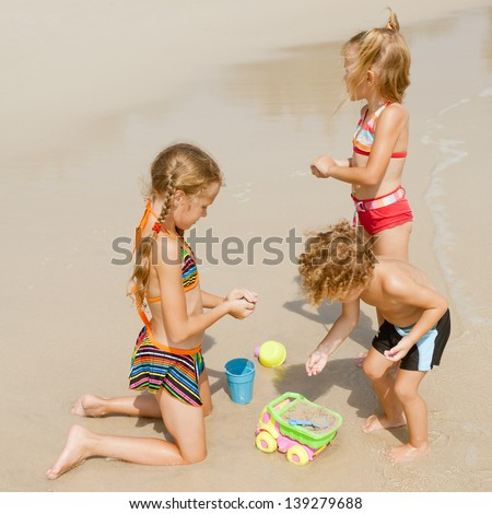 two little girls and little boy playing on the beach - stock photo