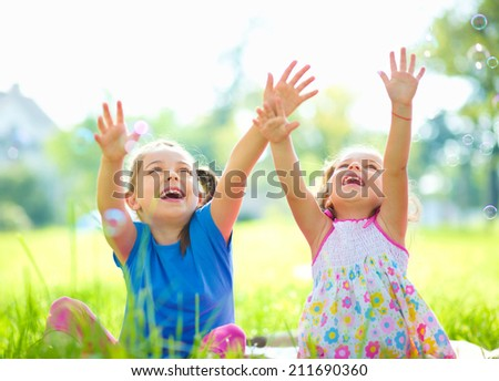 Two little girls are catching soap bubbles, outdoor shoot - stock photo