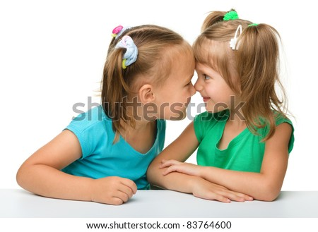 Two little girls are having fun, isolated over white - stock photo