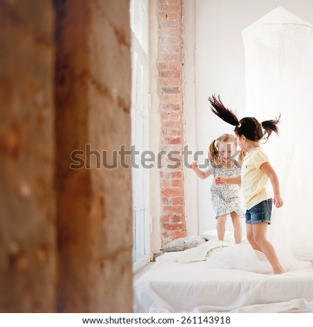 two little girls are jumping on the bed - stock photo