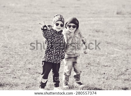 two little girls are playing in spring field - stock photo