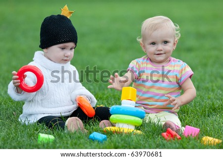 Two little girls are playing with bright toys on the green grass