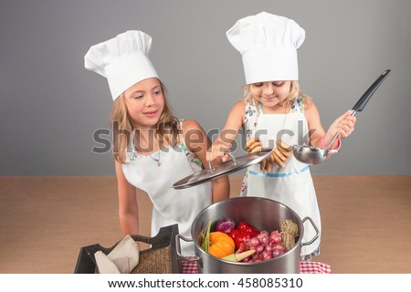 Two little girls are sisters in aprons and chef hats to help in the kitchen to prepare meals. The child puts the vegetables in a large pot. - stock photo