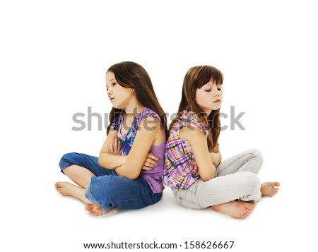 Two little girls back to back in quarrel. Isolated on a white background