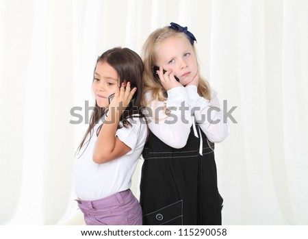 Two little girls calling by phone to each other