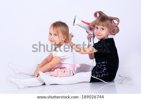 Two little girls  doing hair with a hairdryer isolated on white in studio - stock photo