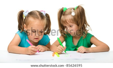 Two little girls draw with markers while sitting at table, isolated over white - stock photo
