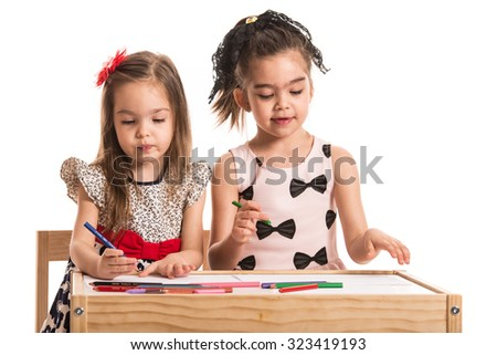 Two little girls drawing on papers at table against white background