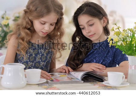 Two little girls drinking tea