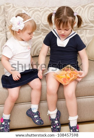 Two little girls eat candies - stock photo