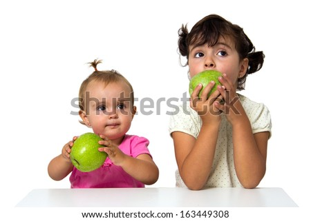 two little girls eating apples isolated on white