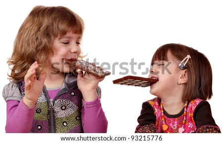 two little girls eating chocolate - stock photo