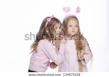 two little girls eating cookies and sharing secrets on a white background - stock photo