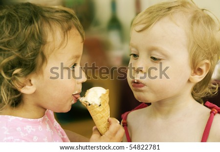 two little girls eating one ice-cream, retro colored - stock photo