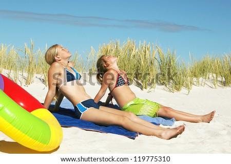 Two little girls enjoy in sunbathing on sandy beach - stock photo