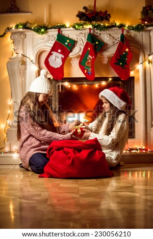 Two little girls fighting for box with Christmas present - stock photo