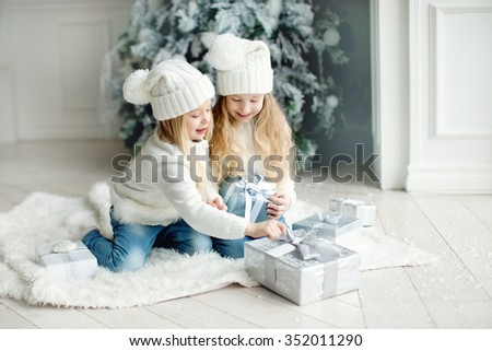 two little girls friends or sisters with long blond hair in white hats and white cardigans and jeans playing andand smiling near the white christmas tree with presents at winter time - stock photo