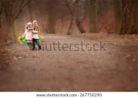 two little girls friends  two green cans with yellow flowers tulips are walking on the road hugging in the park or forest  - stock photo