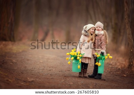 two little girls friends with long blond hair in coats and hats with two green cans with yellow flowers tulips are standing on the road in the park or forest and smiling - stock photo