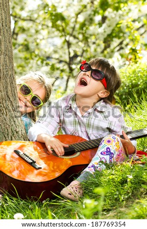 Two little girls have a fun and playing a guitar outdoor - stock photo