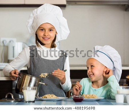 Two little girls having breakfast with oatmeal porridge indoors together