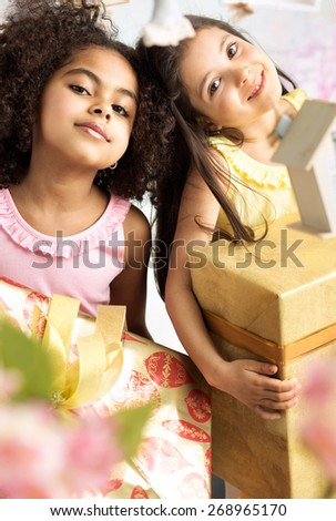 Two little girls holding presents - stock photo