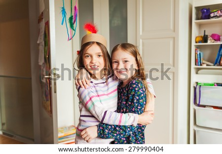 Two little girls hugging in their room - stock photo