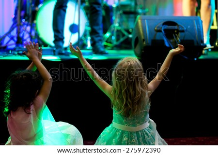 Two little girls in front of stage during rock concert - stock photo