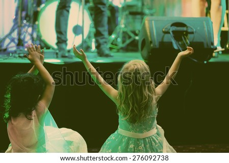 Two little girls in front of stage during rock concert vintage photo - stock photo