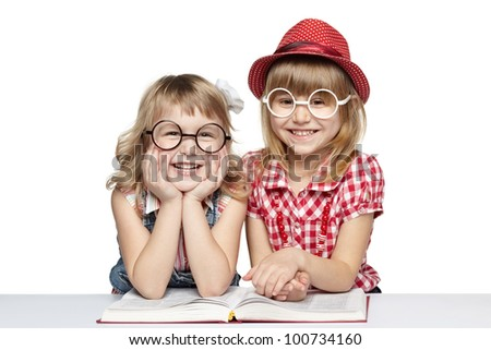 Two little girls in funny eyeglasses reading book, over white background - stock photo