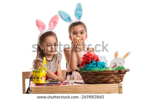 Two little girls in kindergarten sitting at table and painting and decorating Easter eggs - stock photo