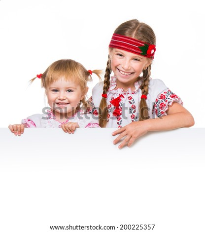 Two little girls in the Ukrainian national costume stand behind white board with space for text