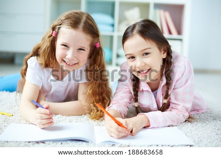 Two little girls looking at camera while lying on the floor and drawing - stock photo
