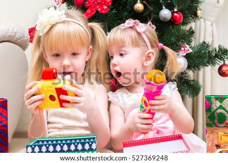 Two little girls looking at Christmas gifts