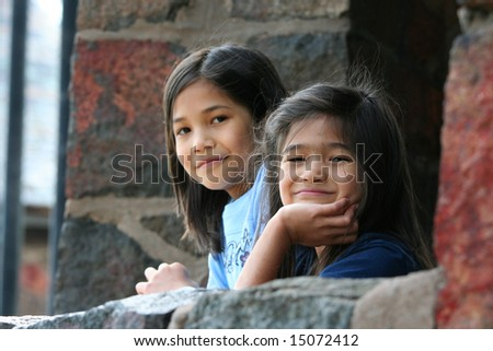 Two little girls looking out over stone wall