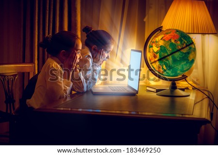 Two little girls looking with amazement at laptop at night - stock photo